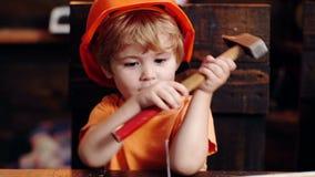 Concetto Handcrafting Il bambino sul fronte occupato gioca con lo strumento del martello a casa in officina Gioco del ragazzo del video d archivio
