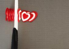 Concetto Il coltello ceramico taglia i biglietti di S. Valentino rossi dei cuori Immagine Stock