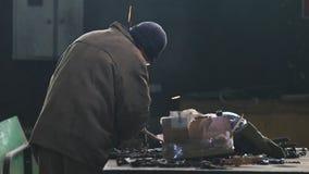 Concetto industriale Un lavoratore dell'uomo che usando una smerigliatrice