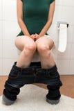 Concetto: La donna sta soffrendo circa la congestione o la diarrea fotografie stock libere da diritti