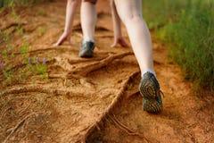 Concetto: le gambe della donna nel moto su un sentiero per pedoni della montagna fotografie stock