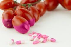 Concetto: manipolazione OMG umana della natura e dei frutti avvelenati relativi Un primo piano di tre pomodori contaminati cambia fotografia stock