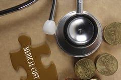 Concetto medico con lo stetoscopio, pezzo di puzzle e monete con Fotografia Stock Libera da Diritti