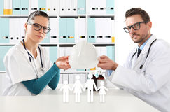 Concetto medico dell'assicurazione malattia, mani di medici con l'icona della famiglia Fotografie Stock Libere da Diritti