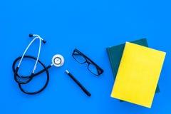 Concetto medico di istruzione Stetoscopio vicino al manuale di medicina ed ai vetri sullo spazio blu della copia di vista superio Fotografia Stock Libera da Diritti