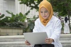 Concetto medico e di radiologia di sanità, - medici graziosi che esaminano computer portatile Immagine Stock