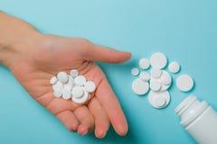 Concetto medico - pillole bianche di forma differente su fondo blu Fotografie Stock Libere da Diritti