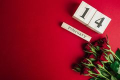 Concetto minimo di giorno di biglietti di S. Valentino della st su fondo rosso Rose rosse e caledar di legno con il 14 febbraio s Immagini Stock