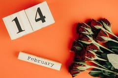 Concetto minimo di giorno di biglietti di S. Valentino della st su fondo rosso Rose rosse e caledar di legno con il 14 febbraio s Fotografia Stock