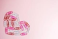Concetto minimo Il simbolo del cuore fatto di cancelleria taglia su fondo rosa Disposizione piana, vista superiore Fotografie Stock Libere da Diritti