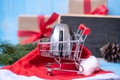 Concetto online di compera di commercio elettronico con il contenitore di regalo di Buon Natale o presente su fondo di legno blu fotografia stock