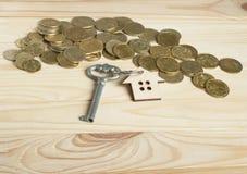 Concetto per la proprietà di affitto o del bene immobile Simbolo della casa con la chiave e delle monete su fondo di legno Fotografia Stock