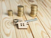 Concetto per la proprietà di affitto o del bene immobile Simbolo della casa con la chiave e delle monete su fondo di legno Fotografia Stock Libera da Diritti