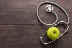 Concetto per la sanità, lo stetoscopio e la mela verde sulle sedere di legno Fotografia Stock Libera da Diritti