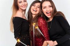 Concetto perfetto di notte di celebrazione Belle giovani donne che esaminano macchina fotografica e che tengono stella filante co fotografie stock