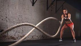 Concetto: potere, forza, stile di vita sano, sport L'istruttore adatto dell'incrocio muscolare attraente potente della donna comb stock footage