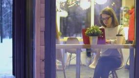 Concetto premuroso Ragazza in un maglione bianco e nei vetri d'uso, lavoranti ad un computer portatile rosso in un caffè vista da stock footage