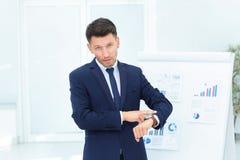 Concetto - prenda la cura del vostro tempo punti dell'uomo d'affari al suo watc Immagini Stock