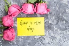 Concetto romantico Le rose rosse e segnare il desiderio con lettere hanno un giorno piacevole su un fondo concreto grigio fotografia stock libera da diritti