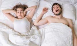 Concetto russante La giovane donna sta coprendo le sue orecchie L'uomo sta russando a letto Fotografia Stock