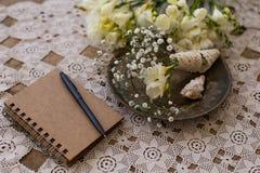 Concetto rustico di pianificazione di nozze Blocco note con la penna nera e smal fotografia stock