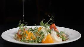 Concetto sano del vegetariano e dell'alimento Chiuda su di olio d'oliva di versamento sopra insalata con il pomodoro, lattuga ver stock footage