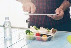 Concetto sano dell'alimento Uomo che fotografa la scatola di pranzo con la f sana Fotografia Stock Libera da Diritti