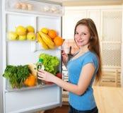 Concetto sano di cibo Dieta Giovane donna vicino al frigorifero fotografie stock