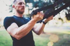 Concetto sano di stile di vita L'atleta muscolare che esercita il trx inserisce su fuori parco soleggiato Grande allenamento di T Fotografia Stock