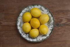 Concetto sano di stile di vita Limoni su un piatto bianco sopra la tavola rustica Fotografia Stock