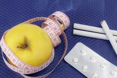 Concetto sano di stile di vita Nastro di misurazione con una mela gialla e sigarette su fondo blu fotografie stock libere da diritti