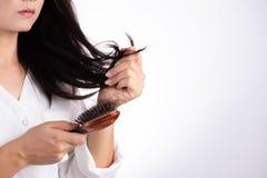 Concetto sano La donna mostra la sua spazzola con i capelli lunghi nocivi di perdita e l'esame dei suoi capelli immagini stock