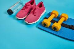 Concetto sano, piano di dieta con le scarpe di sport e la bottiglia di acqua e delle teste di legno su fondo blu, alimento sano e fotografia stock