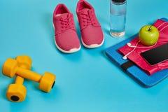 Concetto sano, piano di dieta con le scarpe di sport e la bottiglia di acqua e delle teste di legno su fondo blu, alimento sano e immagini stock libere da diritti