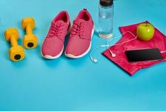 Concetto sano, piano di dieta con le scarpe di sport e la bottiglia di acqua e delle teste di legno su fondo blu, alimento sano e immagine stock