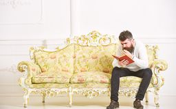 Concetto scandaloso del bestseller Libro di lettura del tipo con attenzione Macho sul libro di lettura concentrato del fronte Uom fotografia stock libera da diritti