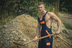 Concetto scavatore Uomo scavatore manuale con la pala Terra scavatrice di vangata Forte zappatore in uniforme funzionante fotografie stock
