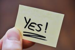 Concetto scopo/di successo - dita che tengono nota con Y scritto a mano fotografie stock