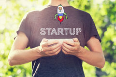 Concetto Startup con il giovane che tiene il suo smartphone fuori Immagini Stock Libere da Diritti