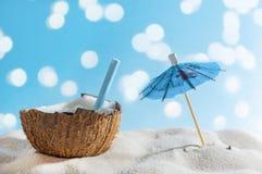 Concetto tropicale di viaggio o della spiaggia: cocktail di estate in ombrello di sole e della noce di cocco fotografia stock libera da diritti