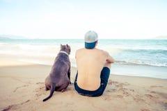 Concetto, uomo e cane di amicizia sedentesi insieme sulla spiaggia al tramonto fotografia stock