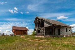Concetto vecchie e nuove case di legno nella campagna su un lotto libero sotto un cielo blu immagini stock