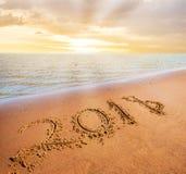 Concetto venente del nuovo anno 2018 Cifre sulla spiaggia di sabbia immagine stock