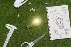Concetto verde del risparmio energetico e della costruzione: alloggi il projecj e lavori gli strumenti sull'erba Fotografie Stock Libere da Diritti