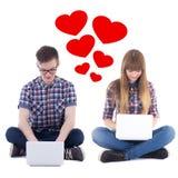 Concetto virtuale di amore - adolescente e ragazza che si siedono con il calcolo Immagini Stock