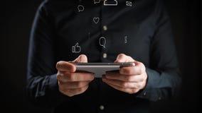 Concetto, vita online digitale e reti sociali Un giovane in una camicia utilizza il suo smartphone per osservare i suoi conti video d archivio