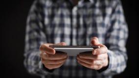 Concetto, vita online digitale e reti sociali Un uomo d'affari in una camicia utilizza il suo smartphone per osservare i suoi con archivi video