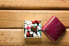 Concettuale della capsula in contenitore di regalo su fondo di legno Immagine Stock Libera da Diritti