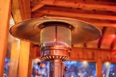 Concevez l'appareil de chauffage d'intérieur brûlant métal-gaz de patio d'acier inoxydable avec le fond brouillé d'enteriour photo libre de droits