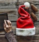 Concezione: Preparazione dei regali di Natale Un uomo tiene un PC della compressa in sue mani ed imballa i regali di Natale Fotografia Stock